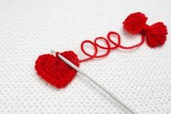Les trois boucles de fil Photo de fête, tricotant avec amour Coeur fait main de crochet et une petite boule rouge de fil sur le c Image libre de droits