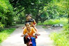 Les trois garçons conduisant sur la bicyclette Photographie stock