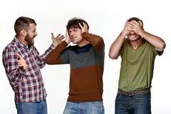 Les trois hommes regardant avec différentes émotions Photographie stock