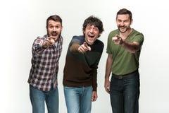Les trois hommes sont souriants, regardants et se dirigeants l'appareil-photo Photos libres de droits