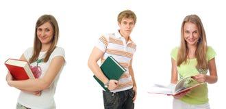 Les trois jeunes étudiants d'isolement sur un blanc photographie stock