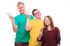 Les trois jeunes montrant le signe et le sourire de victoire image stock