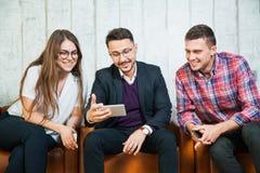 Les trois jeunes observent la vidéo mobile au téléphone intelligent Photographie stock