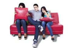 Les trois jeunes regardant la TV Photo stock