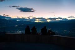 Les trois jeunes s'asseyant sur la colline donnant sur la capitale de la Géorgie, Tbilisi tandis que le soleil va vers le bas der photographie stock libre de droits