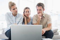 Les trois jeunes travaillant sur l'ordinateur images libres de droits