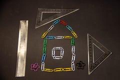 Les trombones colorés ont garni d'une maison sur un fond noir image stock