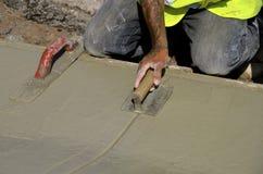 Les truelles de travailleur de Concerete ont mouillé le ciment Photographie stock libre de droits