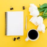 Les tulipes blanches fleurit, carnet, le stylo, agrafes avec la tasse de café sur le fond jaune Configuration plate, vue supérieu Photo stock