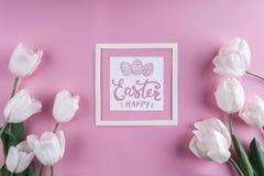 Les tulipes blanches fleurit sur le fond rose avec la carte de Pâques Ressort de attente Images libres de droits