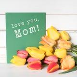 Les tulipes colorées de ressort en rouge et jaune avec une carte verte avec amour vous, souhaits de maman avez embouti là-dessus  Photographie stock libre de droits