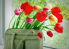 Les tulipes de fleurs et des femmes mettent en sac sur un filon-couche de fenêtre de fenêtre Photos stock