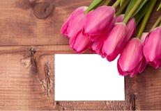 Les tulipes fleurit avec la carte de voeux au-dessus de la table en bois Photographie stock libre de droits