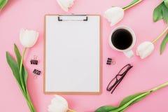 Les tulipes fleurit avec la tasse de café, de presse-papiers et de verres sur le fond rose Concept de Blogger ou d'indépendant Co Photos libres de droits