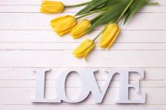 Les tulipes fraîches de jaune de ressort fleurit et l'amour de mot sur le woode blanc Photos libres de droits