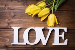 Les tulipes fraîches de jaune de ressort fleurit et l'amour de mot sur le woode foncé Photos stock