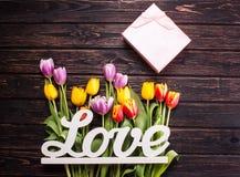 Les tulipes fraîches de ressort fleurit et l'amour de mot sur le backgro en bois foncé Photographie stock libre de droits