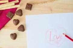 Les tulipes légères en bois de coeur et de cadeau de bonbons au chocolat à fond waffles, papier de points de poli de mite de tiss Photos stock