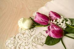 Les tulipes pourpres avec la rose et la jacinthe de blanc sur le coin ont brodé la nappe Photos stock