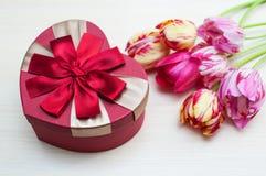 Les tulipes roses et le coeur enferment dans une boîte la forme d'isolement sur le fond blanc Image libre de droits