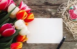 Les tulipes se rassemblent sur le fond en bois de planches de grange foncée Photographie stock libre de droits