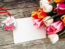 Les tulipes se rassemblent sur le fond en bois de planches de grange foncée Photo libre de droits