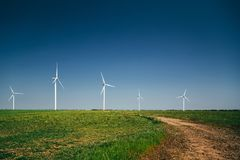 Les turbines de générateurs de vent l'été aménagent en parc en vallée verte sous le ciel bleu photographie stock libre de droits