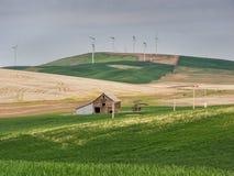 Les turbines de vent sur la colline complète avec les champs et la grange de blé Photo stock