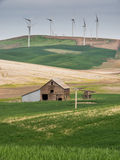 Les turbines de vent sur la colline complète avec les champs et la grange de blé Photos stock