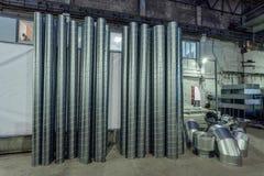 Les tuyaux d'acier et d'autres pièces pour la construction des conduits d'air industriel conditionnent le système dans l'entrepôt Image libre de droits