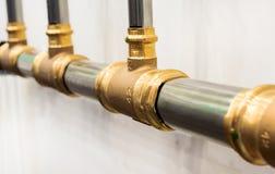 Les tuyaux en métal reliés par les pièces en t en laiton Photo stock