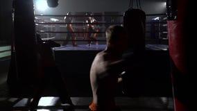 Les types bat une poire, à l'arrière-plan dans l'anneau va des kickboxers de boxe d'entraînement banque de vidéos