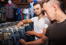 Les types choisissent des jeans Photos stock