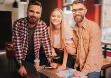 Les types et la fille heureux sont table proche debout avec des matériaux d'affaires et sembler simples Ils sourient Images stock