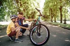 Les types ont une petite pause pendant le voyage de theit sur des bicyclettes Ils se reposent à la frontière de la route L'homme  image stock