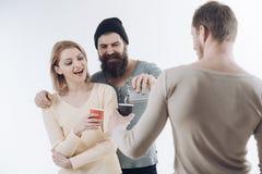Les types tiennent la tasse, flacon avec de l'alcool, parlent La société des amis gais dépensent des loisirs avec des boissons Co photo stock
