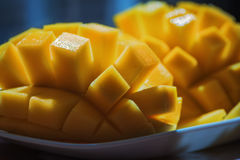 Les ubes mûrs frais naturels de mangue, tranches se ferment, macro tir Sur le fond bleu-foncé ou noir Sur le rustique photos libres de droits