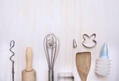 Les ustensiles réglés de cuisson avec la goupille, spatule, battent, cuillère en bois encochée sur le fond en bois blanc, vue sup Images libres de droits
