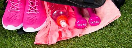 Les vêtements et les accessoires roses pour la forme physique, une bouteille de l'eau, dans des sports mettent en sac, sur le fon Images libres de droits