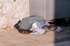 Les vêtements et les chaussures gaspillent à gauche près dans le récipient de déchets sur la rue photographie stock