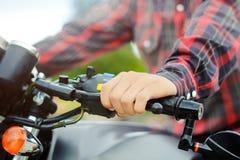 Les vêtements pour hommes de main de Closup une chemise de plaid rouge, conduisent une moto de vintage Photographie stock libre de droits