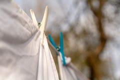 Les v?tements blancs ont tra?n? pour s?cher sur une ligne de lavage et attach? par les pinces ? linge pendant le jour ensoleill?  photo stock