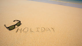 Les vacances écrites dans le sable à la plage ondulent à l'arrière-plan Photos libres de droits
