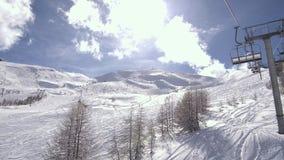 Les vacances d'hiver voyagent sur le télésiège au-dessus de la station de sports d'hiver clips vidéos