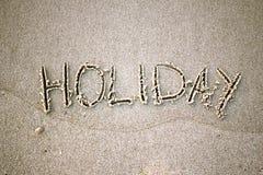 Les vacances de mot dans le sable Photographie stock