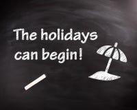 Les vacances peuvent commencer l'expression sur le tableau noir Photo stock
