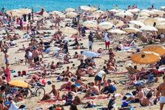Les vacanciers les prennent un bain de soleil sur la plage à Barcelone Photographie stock libre de droits