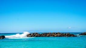 Les vagues de l'océan pacifique se brisant sur les roches des barrières à l'homme ont fait des lagunes sur le rivage de Ko Olina photos libres de droits