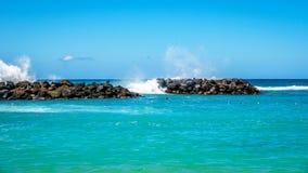 Les vagues de l'océan pacifique se brisant sur les roches des barrières à l'homme ont fait des lagunes sur le rivage de Ko Olina photographie stock