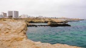 Les vagues de mer de l'eau bleue éclaboussant au sujet du cap en pierre sur la ville aménagent le fond en parc banque de vidéos